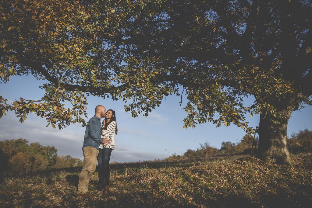 Séance photo en amoureux en exterieur - couple s'embrasse sous grand arbre - Photographe couple Toulouse