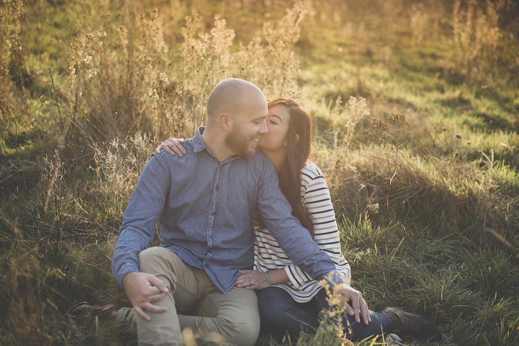 Séance photo en amoureux en exterieur - couple assis dans plantes sauvages s'embrasse - Photographe couple Toulouse