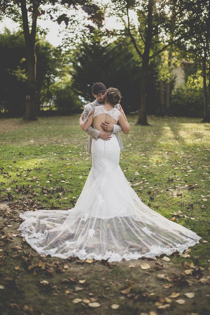 Reportage mariage automne Saint-Gaudens - calin des mariés avec longue traine - Photographe Saint-Gaudens
