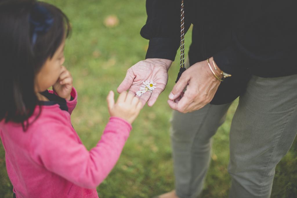 Reportage famille automne - petite fille met des paquerettes dans les mains de sa tata - Photographe famille Haute-Garonne