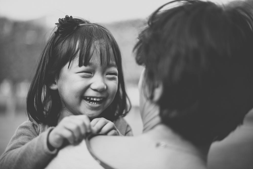 Reportage famille automne - petite fille rit dans les bras de sa maman - Photographe famille Haute-Garonne
