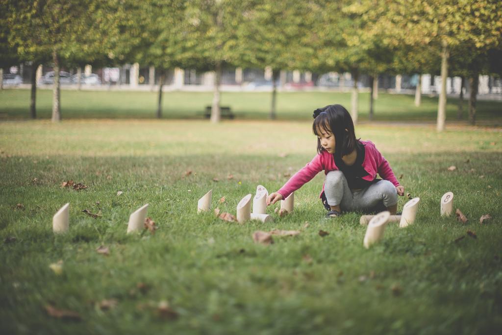 Reportage famille automne - petit fille ajuste les quilles du molkky - Photographe famille Haute-Garonne