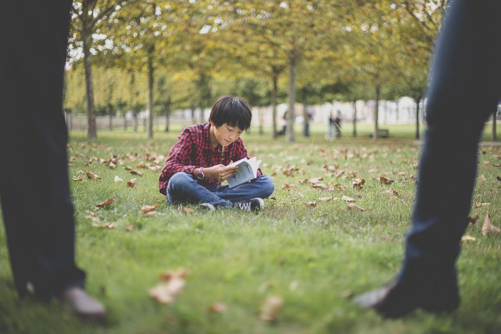 Reportage famille automne - petit garçon assis dans l'herbe bouquine - Photographe famille Haute-Garonne