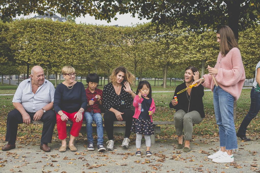 Reportage famille automne - famille assise sur banc fait des bulles de savon - Photographe famille Haute-Garonne