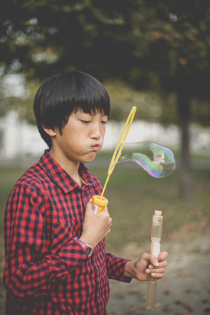 Reportage famille automne - petit garçon fait une grosse bulle de savon - Photographe famille Haute-Garonne