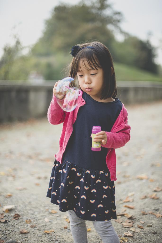 Reportage famille automne - petite fille fait des bulles de savon - Photographe famille Haute-Garonne