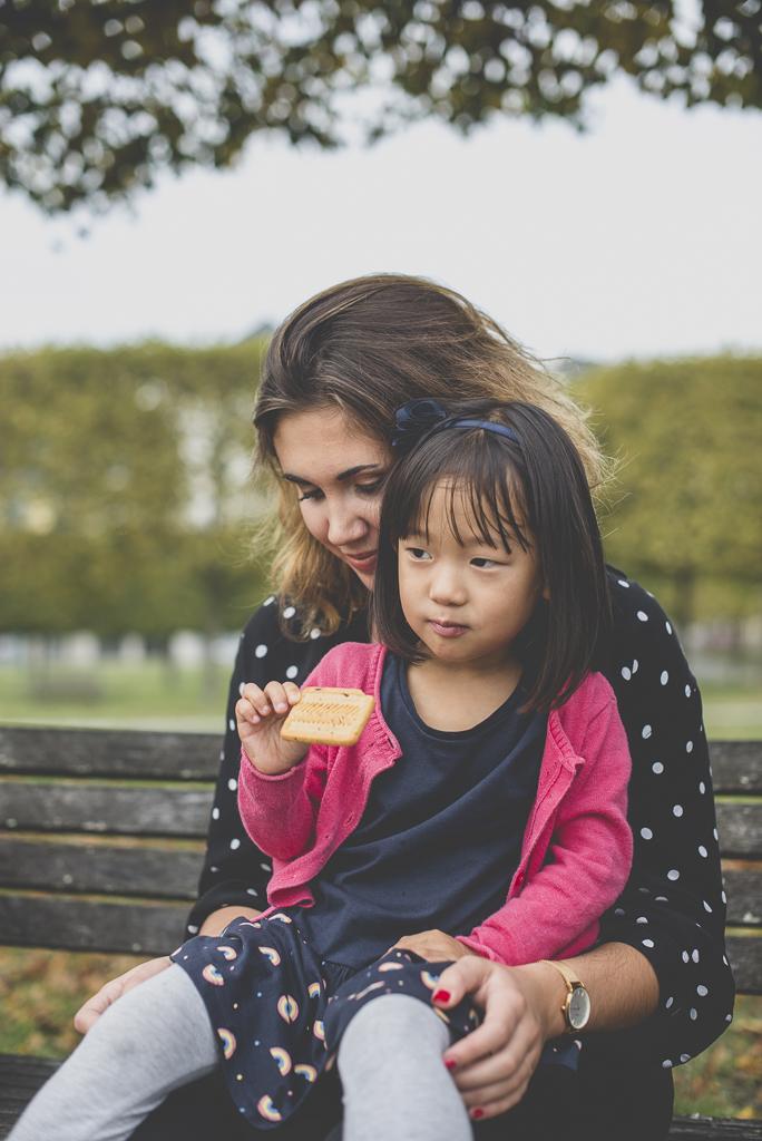 Reportage famille automne - petite fille assise sur genoux de sa cousine - Photographe famille Haute-Garonne
