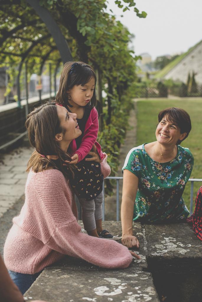 Reportage famille automne - enfant et sa famille rient ensemble - Photographe famille Haute-Garonne