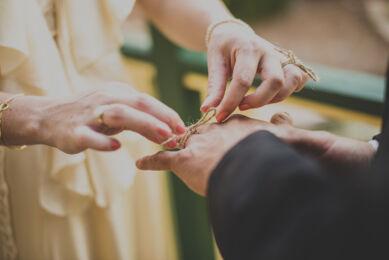 rozimages - photographie de mariage - gros plan sur les mains de la mariée faisant un noeud autour du doigt du marié avec un bout de ficelle - Broome, Australie