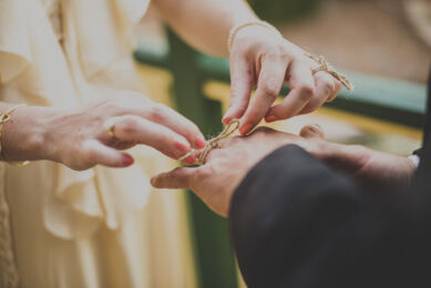 rozimages - wedding photography - close-up on hands of bride and groome, bride tying a knot with a piece of sting around groom's finger - Broome, Australia