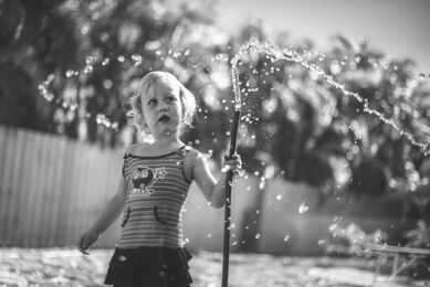 Girl playing with a hose in the garden. Family photographer.