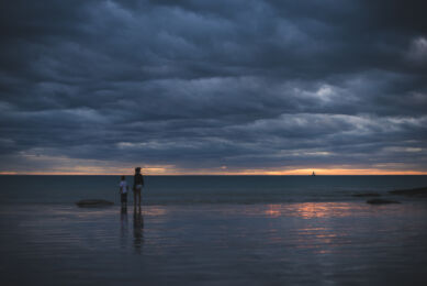 Deux enfants regardant approcher une tempête de plage au coucher du soleil. Photographe Rozenn Hamoniau