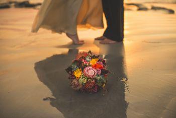 Bouquet de fleurs sur la plage et pieds du couple marié dans le fond. Photographe de Mariage Toulouse.