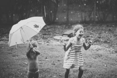 Séance photo en famille à domicile - deux filles jouent sous la pluie - Photographe famille