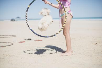 Séance photo de famille sur la plage - fille tenant un cerceau dans lequel un petit chien saute - Photographe de famille